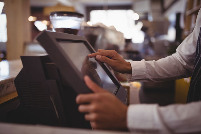 Restaurant Employee taking order from a digital cash register
