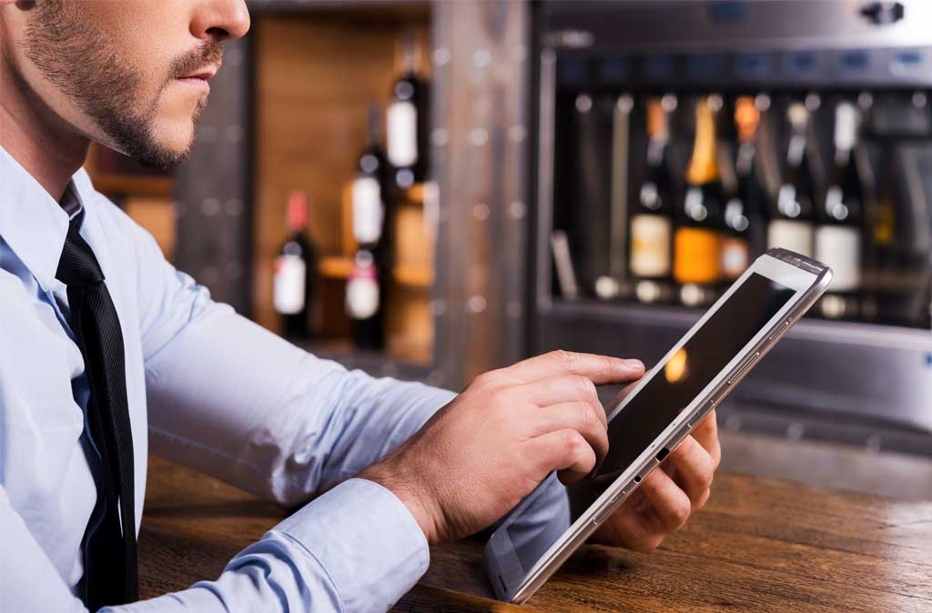 restaurant owner checking employee attendance on ipad